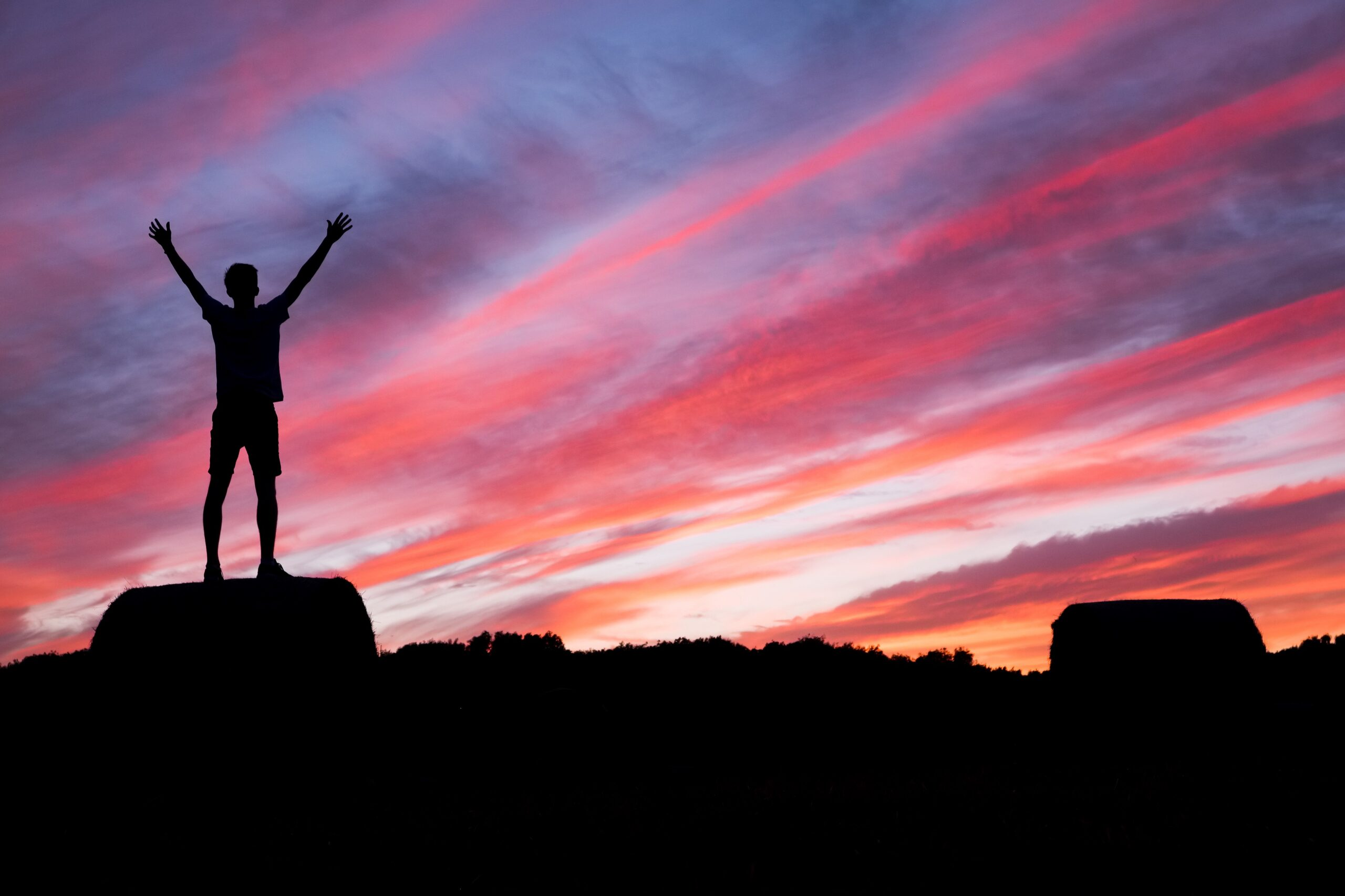 Man standing on mountain top with hands in the air